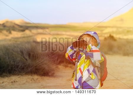 family travel- little girl with binoculars exploring scenic mountains