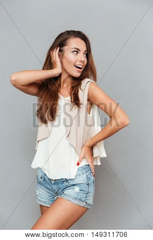Smiling young pretty girl posing and looking away isolated on a gray background