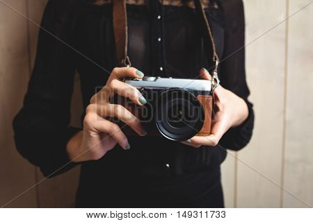 Mid-section of woman standing with camera against texture background