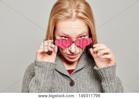 Young blond woman removing her pink heart glasses