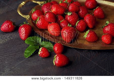 Ripe strawberries on a tray and dark wooden background