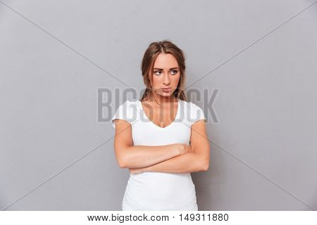 Sad upset young woman standing with arms crossed over grey background