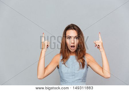 Amazed shocked young woman pointing up with both hands over grey background