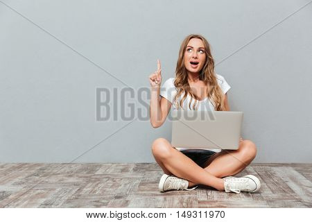 Portrait of a smiling woman sitting on the floor with laptop and pointing finger up isolated on gray background