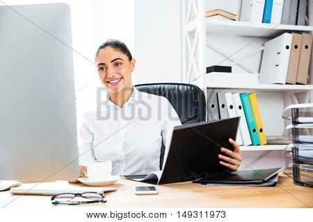 Smiling charming businesswoman holding documents and looking at computer screen while sitting at the office desk