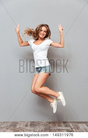 Full length portrait of a happy smiling woman jumping and showing v gesture isolated on a gray background