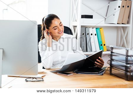 Beautiful smiling businesswoman reading documents while sitting at the office desk