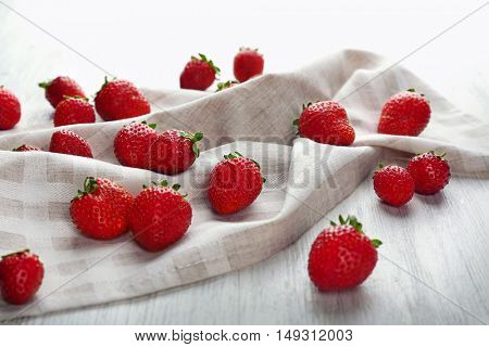 Fresh strawberries on napkin and white wooden background
