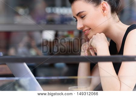 selective focus of a modern woman sitting in front of her laptop outdoors