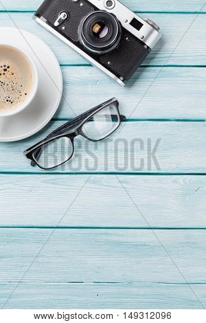 Wooden table with camera, glasses and coffee. Top view with copy space.