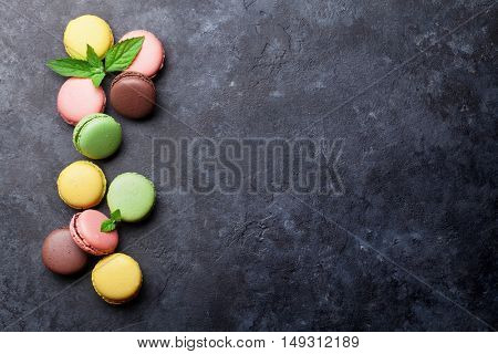 Colorful macaroons on stone table. Sweet macarons. Top view with copy space for your text.