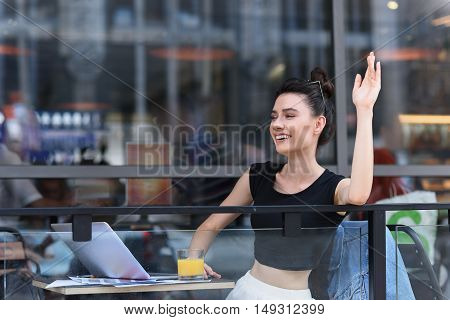 relaxed woman in a cafe welcomes her friends