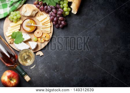 White wine, grape, bread, honey and cheese on stone table. Top view with copy space