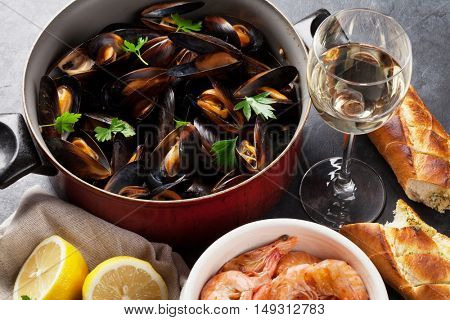Mussels, shrimps and white wine on stone table