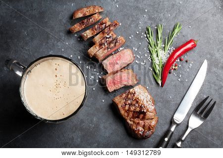 Grilled sliced beef steak and beer on stone table. Top view