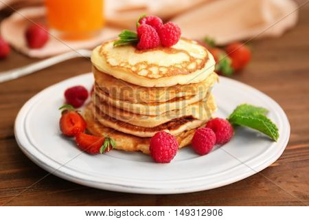 Tasty pancakes with berries on plate