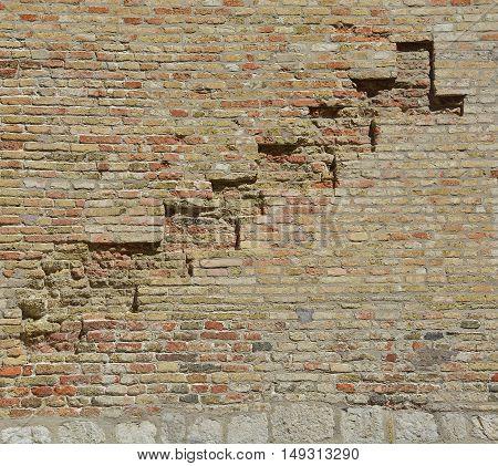 A brick wall in an old historic building in the north east Italian town of Pordenone in Friuli Venezia Giulia