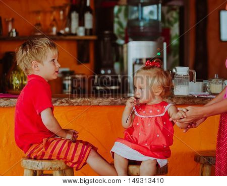 cute little boy and toddler girl sitting at the bar, kids eating out