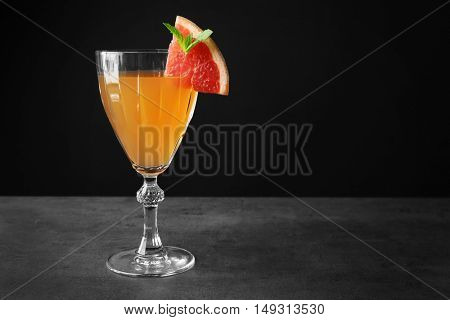 Delicious cocktail with grapefruit slice on gray table