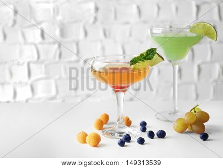 Delicious cocktail with berries on white table