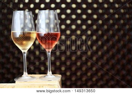 Glasses of wine on blurred bottle wall background