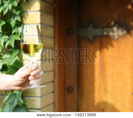 Male hand holding glass of white wine, outdoor