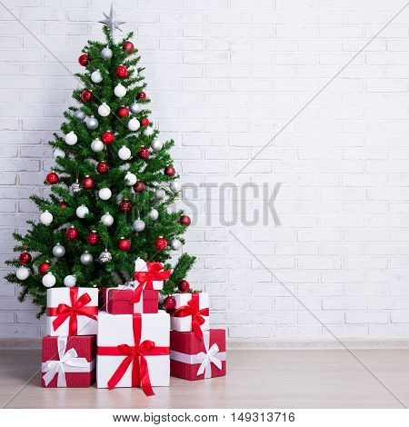 Decorated Christmas Tree With Colorful Balls And Gift Boxes Over White Brick Wall