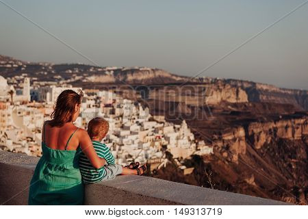 mother and little son looking at Santorini, Greece