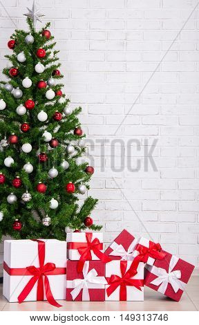 Gift Boxes And Decorated Christmas Tree With Colorful Balls Over Brick Wall