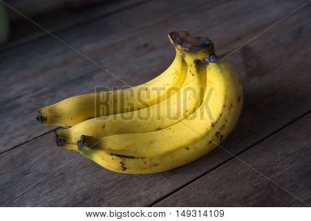 ripe yellow Fresh bananas on wood background, light and Shadow