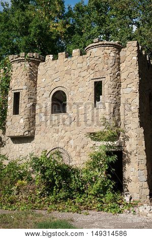 old ruined castle in the summer forest background.