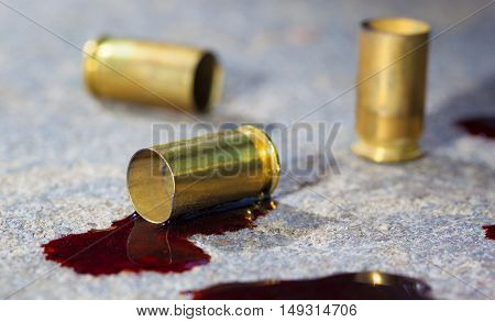Brass from a pistol that is on concrete with blood around