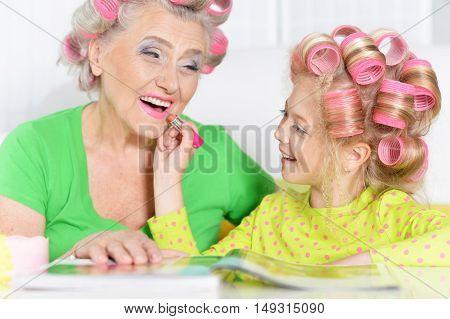 Senior woman and granddaughter doing make up at home