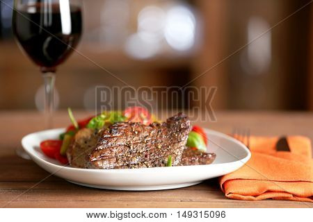 Gourmet steak with vegetables and glass of red wine on wooden table