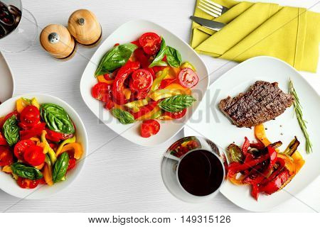 Tasty steak with vegetable salad and glass of wine on table