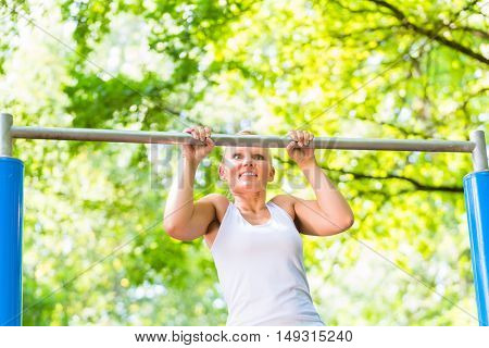 Woman exercising at high bar for better outdoor fitness