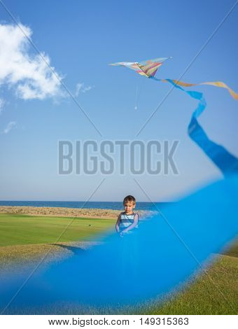 Little boy on summer vacation having fun and happy time flying kite on the sea beach