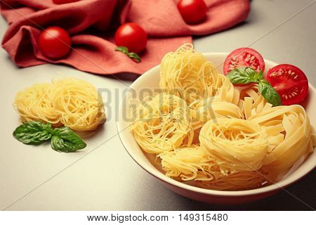 Bowl with pasta nests and cherry tomatoes on table, close up