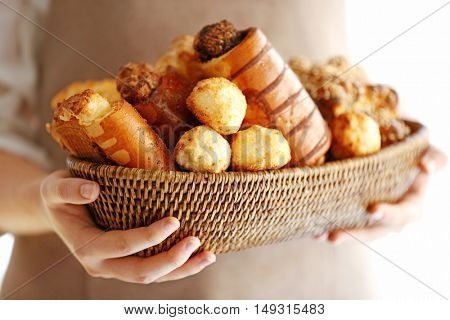 Woman holding fresh bakery products, closeup