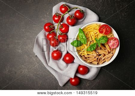 Bowl with different kinds of dry pasta and tomatoes on table