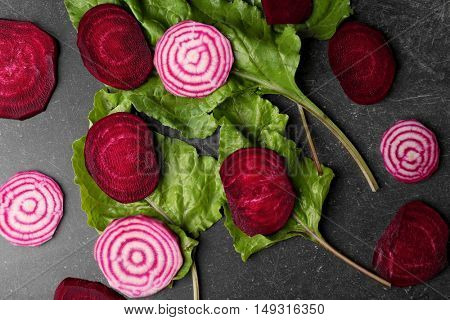 Fresh beetroots with tops on grey background