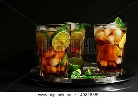 Metal tray with cuba libre cocktails on dark background