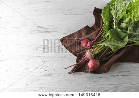 Bunch of fresh beets on brown napkin and light wooden background