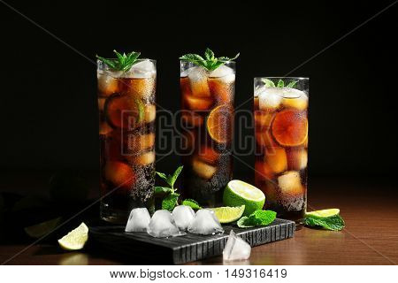 Cuba Libre cocktail with lime, ice, mint and tray on wooden table