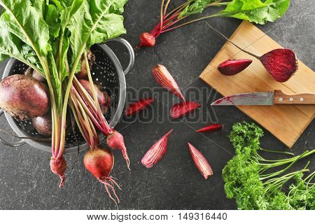 Bunch of fresh beets in a colander on grey background