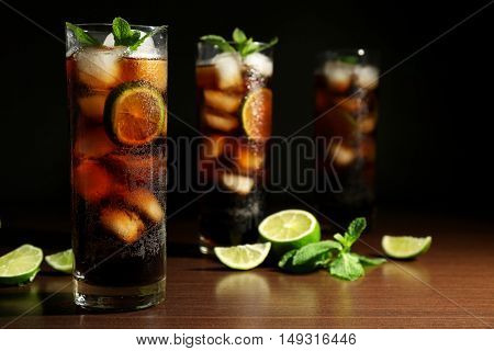 Cuba libre cocktails with lime and mint on wooden table