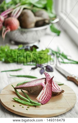 Fresh sliced beet with mangetout on wooden board