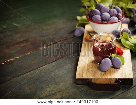 Plums and jar of jam on table. Homemade bio food concept
