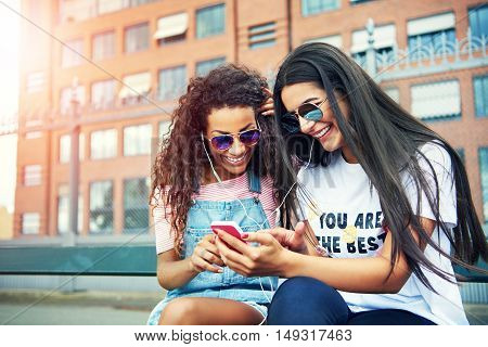 Happy young women sharing listening time for music or video on a pink phone while seated outside
