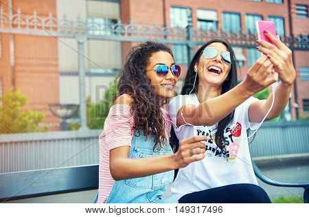 Joyful young female friends in sunglasses and summer outfits posing for self portrait photos on bench near large brick building